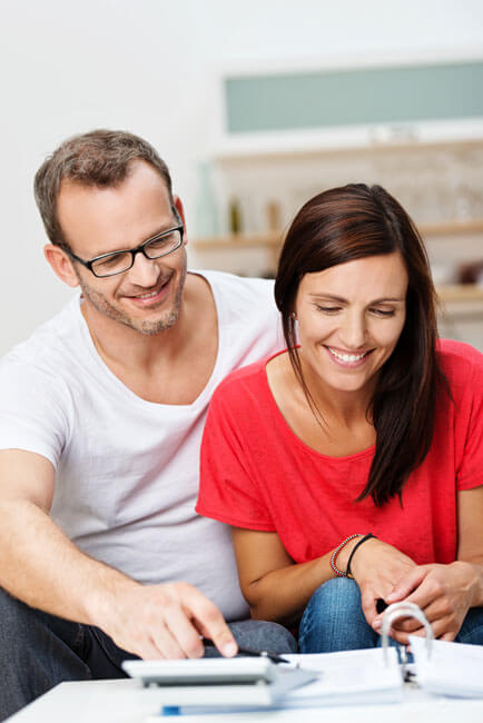 Young couple examining an estate plan created by Sandi Persoon, an Advice Only financial planner who helps clients young and old create plans that allow then to achieve their life goals.